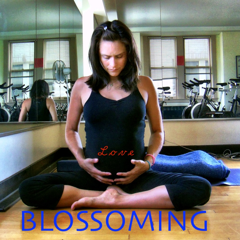 A 7 month pregnant yogini sits in siddhasana holding her belly