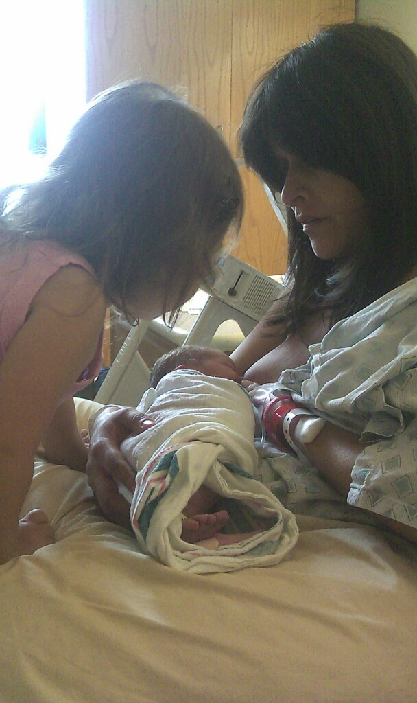 Mother nursing baby sister as big sister meets her for the first time